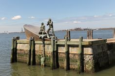 The American Merchant Mariners' Memorial sculpture, located in the Hudson River west of the park, is sited on a stone breakwater just south of Pier A and connected to the pier by a dock. It was designed by the sculptor Marisol Escobar and dedicated on 8 October 1991. The bronze sculpture depicts four merchant seamen with their sinking vessel after it had been attacked by a U-boat during World War II. One of the seamen is in the water, and is covered by the sea with each high tide.