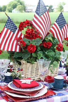 Patriotic Table setting (Memorial Day, Flag Day, 4th of July) A basket of red flowers adorned with 3 American flags, red/white/blue checked table cloth, Blue cups, Red napkins with stars on them, mix matched plates