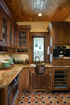 The hand chiseled granite sink ties in with the rustic nature of the mountain-set timber frame home.