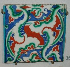Tile. Made of red, cobalt, green, turquoise, black glazed pottery.