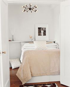 White bedroom + calm neutral palette + dramatic chandelier