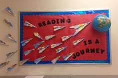 """Bulletin board created by my mom @guevara it's airplanes and an inflatable globe. """"Reading is a journey!"""""""