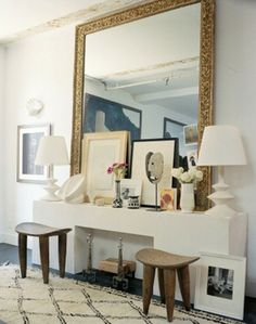 Home of photographer Francois Halard.  Luxe eclectic with Beni Ourain rug, Giacometti plaster lamps, Senufo stools, huge carved gilded mirror...  Swoon.