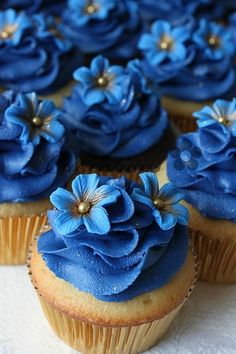 Blue cupcakes with flower accents. Price for buttercream only without flower $1 each. Price with buttercream + flower $1.75 each. White flowers with green centers might look good too so they stand out more against the dark blue.