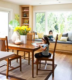 Comfortable & Modern- New windows and built-in cabinetry turn this dining area into an airy work space for the family. Outside of meal times, the table is a place to color and craft. Bench seating beneath the window is piled with pillows for a comfy spot to read.