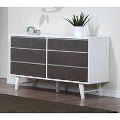 This dresser features six convenient sliding drawers that sit on metal glides for easy opening and closing. With a unique color scheme of light charcoal grey and butter white, the dresser stands on slanted legs for a unique design.
