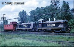 Another former set of Burlington cow-calves, #9412B and #9401A, roll through the yard in Minneapolis with a waycar (CB&Q's term for a caboos...