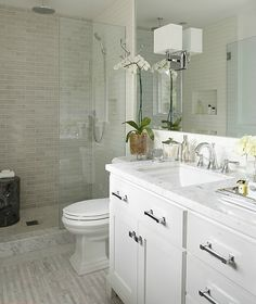 modern white small bathroom design idea- tile in shower. Mirror over vanity which looks similar to an Adel cabinet.