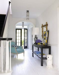 White Foyer: Adler wanted the foyer to have a clean, breezy look. Walls are painted Pocket Watch White by Ralph Lauren; the floor is marine deck paint.