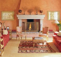 Tuscan limestone mantel flanked by cushions in Osborne & Little fabric. Tuscan 19th-c. prints. Locally made sofas in C&C Milano linen. Oak side tables by Piero Castellini. Church candlestick as lamp. Kilim on sisal rug. Louis XV chairs in Pierre Frey fabric. Ottoman in cashmere fabric by C&C Milano. Tole-style painted brass floor lamp. INTERIOR DESIGN BY PIERO CASTELLINI BALDISSERA    - Veranda.com