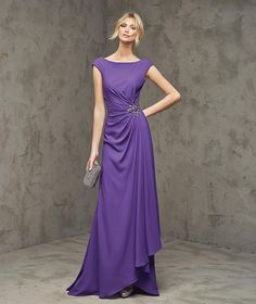 FABIANA- Flared georgette dress with cap sleeves. Bodice with bateau neckline, draped at the waist and decorated with a gemstone appliqué. Deep round opening at the back.