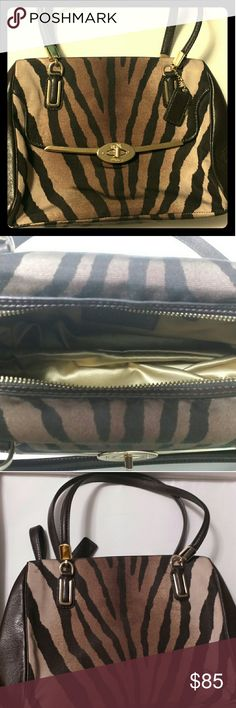 """Coach Madeline Zebra striped Satchel handbag NWOT Authentic Coach satchel with Zebra stripes. Just used once for shopping. No stains or marks. Has two shoulder handles made of leather. The bag has leather trim on the sides and rest is made up of fabric. Has one outer turn lock pocket and two pockets in the main compartment of the bag. Top of the bag is zip closure.  Handles have approx. 7.5"""" drop. Coach Bags Satchels"""