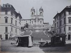 1865 circa autore non identificato . Piazza di Spagna, vista verso la scalinata di Trinità dei Monti con chioschi e personaggio seduto in primo piano.