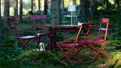 Red MÄLARÖ table and chairs in a woodland setting - with solar lamp