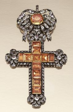 PASTE PENDANT, PORTUGUESE LATE 18TH CENTURY.  Designed as a Latin cross, suspended from a tied ribbon bow surmount, similarly decorated to the cardinal points, set with foil backed table-cut and cushion-shaped paste of yellow tint, highlighted with circular-shaped near-colourless paste.