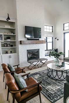Gorgeous modern farmhouse living room designed by Sita Montgomery Interiors - white brick fireplace simple wood mantel leather slingback chairs layered rugs circular coffee table and sconce lighting above open shelving - April 27 2019 at Design Living Room, Family Room Design, Home Living Room, Living Room Furniture, Living Spaces, Apartment Living, Apartment Ideas, Cozy Apartment, Living Room Fire Place Ideas