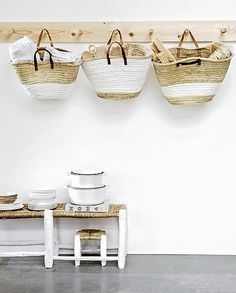 Moroccan market baskets painted with white stripes + the simple little straw and wood stools with legs painted white.