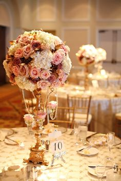 Gorgeous gold candelabra draped in pearls and topped by floral arrangements