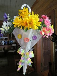 I first saw the umbrella with flowers in it as a door hanger on Pinterest.  I purchased baby umbrellas, added flowers from the dollar tree, used ribbon I had at home & hot glued the buttons.  Reworking old umbrellas would work as well! ~NiQi