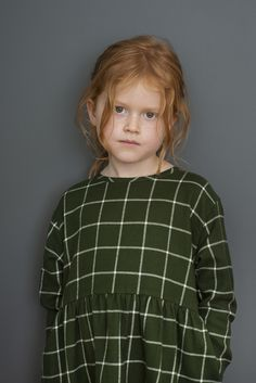 Soft brushed cotton dress in deep green and cream checks. The dress has a round neck and a coconut button in the neck. Lovely cutline that gives wrinkle-effect and good width in the skirt. It has pockets in both side seams.