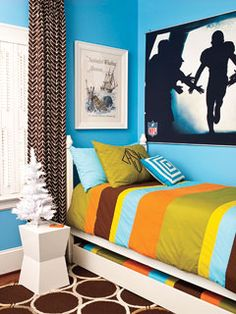 colorful, layered boy's bedroom with a fun football poster above the bed.