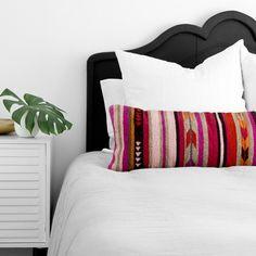 Tête de lit noire mise en valeur grâce au blanc, une plante et du linge coloré