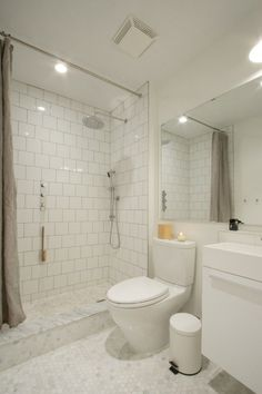 All-White Bathroom Renovation | Remodelista.  Using an offset pattern for the standard square tiles really adds a lot of interest to a very economical product. The marble octagon flooring also helps. :)