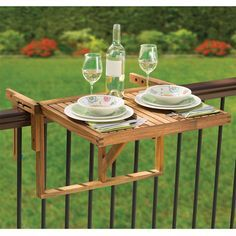 """The Instant Wooden Deck Table - This is the wooden table that instantly mounts over a deck or balcony railing to provide a platform for al fresco dining, a party's drink station, or a card game. Available only from Hammacher Schlemmer and made from naturally water-resistant acacia stained to impart a golden luster to the wood, the table unfolds to form a 29 1/2""""-wide x 23 1/2""""-deep adjustable platform that hangs between 3"""" and 8"""" below a railing's top."""