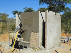16. Mike, the builder, plasters the outside wall of the fourth and final double latrine to be constructed.