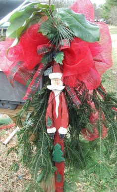 Christmas Mailbox Decoration - Vintage Wooden Santa and Bright Red Deco Mesh Bow with Plaid Ribbon top off a large bunch of Evergreen Fir.