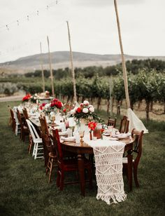 A fall-inspired tablescape with jewel tones and pops of red for this boho wedding in a vineyard in Colorado with a macrame table runner for the ultimate boho chic touch.