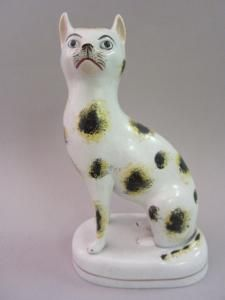 """Seated Cat. Yellow, Black and White Spotted Cat on Base. Circa 1845. 7-1/4"""" (18.5cm)."""