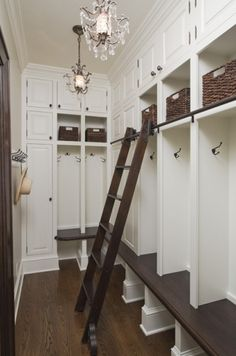 Mudroom | Shelves across the top of the ceiling and a rolling ladder to reach them.