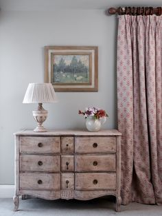 This Gustavian Chest of Drawers can be sold separately or add a top for a dresser. This truly beautiful piece of furniture can be used in many different rooms. Our large carved lampbase balances the pleated linen shade with the blue white spot jug of freshly cut flowers. Curtain in Red Moonflower with warm seas paint.