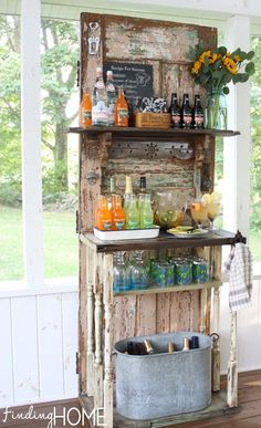 DIY Outdoor Beverage Bar Station using a recycled door with added shelves.  Notice the bottle opener near the top left of the door.  I love this!!