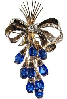 This is a classic pin to wear on a jacket or a coat. Nine open backed cobalt rhinestones are arranged three dimensionally giving depth to this pin.