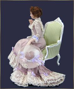 Her elegant dress is made of lilac silk, trimmed with lace and silk bows.  Her hat is made of matching silk and lace, decorated with a silk ...