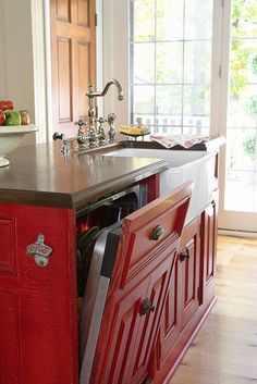 Country kitchen with red painted cabinets, a hidden integrated dishwasher and a farmhouse sink  (via Savvy Kitchen Island Storage - Traditional Home®)