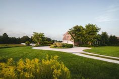 Vibrant wildflowers and a spacious yard surround a gorgeous plantation home, which also features a long covered porch and a long pool. Hydrangeas and thick ornamental grasses are key components of the yard, as is a comfortable hot tub.