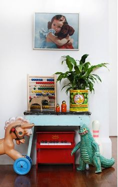 eclectic kids room with mini piano, vintage painting, plants