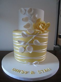 Elegant two tier wedding cake. yellow bottom tier, white top tier with a single yellow rose with white rose leaves
