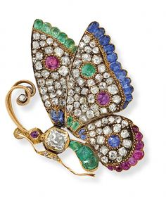 A diamond emerald sapphire and ruby butterfly pin  Designed as the profile of a butterfly in flight, the body set with a cushion-cut diamond and calibre-cut emeralds to circular-cut ruby eyes and diamond highlights, the wings pavé-set with diamonds and decorated with variously-cut rubies, sapphires and emeralds, length 4.3 cm, c. 1870, French assay marks, later pin fitting.