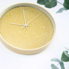 Trendy oker gele klok met houtkleurige rand en witte wijzers. Deze klok is van Dutch Sprinkles en shop je online. Heel fijn: de klok tikt niet en is dus ook geschikt voor in de slaapkamer.