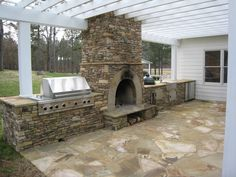 I really like the built in grill and the pergola that surround this fireplace
