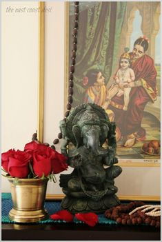 """A bunch of red roses packed tightly into the antique brass mortar. A Green Aventurine Natural Stone Ganesha statue with a Ravi Varma's """" Yashoda & Krishna"""" oleograph"""