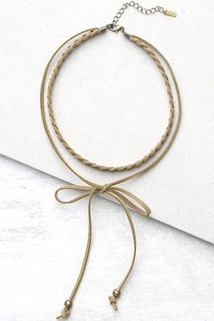 """The adventure awaits in the Everyday is a Winding Road Tan Suede Layered Choker Necklace! A braided vegan suede choker sits above a tying cord with antiqued gold beads. Shortest layer measures 12"""" around with a 2"""" extender chain."""