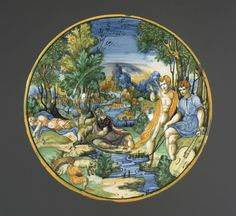 Plate with deep well. Earthenware covered front and back with presumed tin glaze. Painted on the front with a landscape with trees; to the left, Eurydice lying dead, centre a river god, right, Orpheus with a guitar being told of Eurydice's death. Subject derived from Ovid; the scene and inscription on the reverse from Poliziano's `Favola di Orfeo'.
