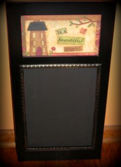 "Black pressed wood hanging panel with an inset chalkboard, topped with a 5"" x 9"" art print of a primitive house done in a decoupage style, which reads ""It's a beautiful world"". 24"" tall and 12"" wide, chalkboard slate is 12-1/2"" tall and 9"" wide. Sawtooth hanger on back. Love this!!! So Pretty!! $24.99"