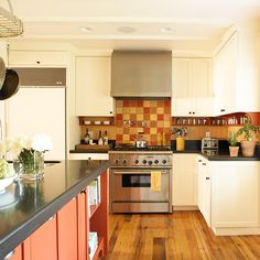 Kitchen with Autumnal Color Palette: Warm and dramatic, this kitchen gets its autumnal glow from a red-orange island and ivory cabinets topped with honed black granite. The multicolor field-tile backsplash blends the islands' fiery red with golden tones that complement the hardwood floors.