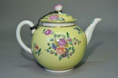 Teapot and cover; porcelain; yellow ground and flowers; some gilding; chain attaching lid.